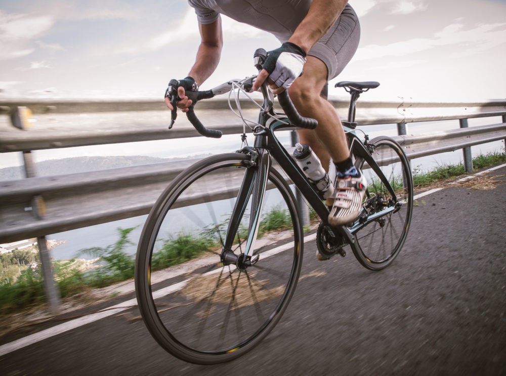 Detail of a road bike with a cyclist pedaling on a road.
