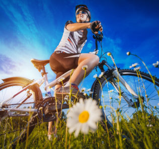 Happy Young Woman riding bicycle outside. Healthy Lifestyle.