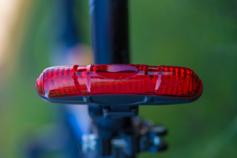 Red rear bicycle lamp with green blur background