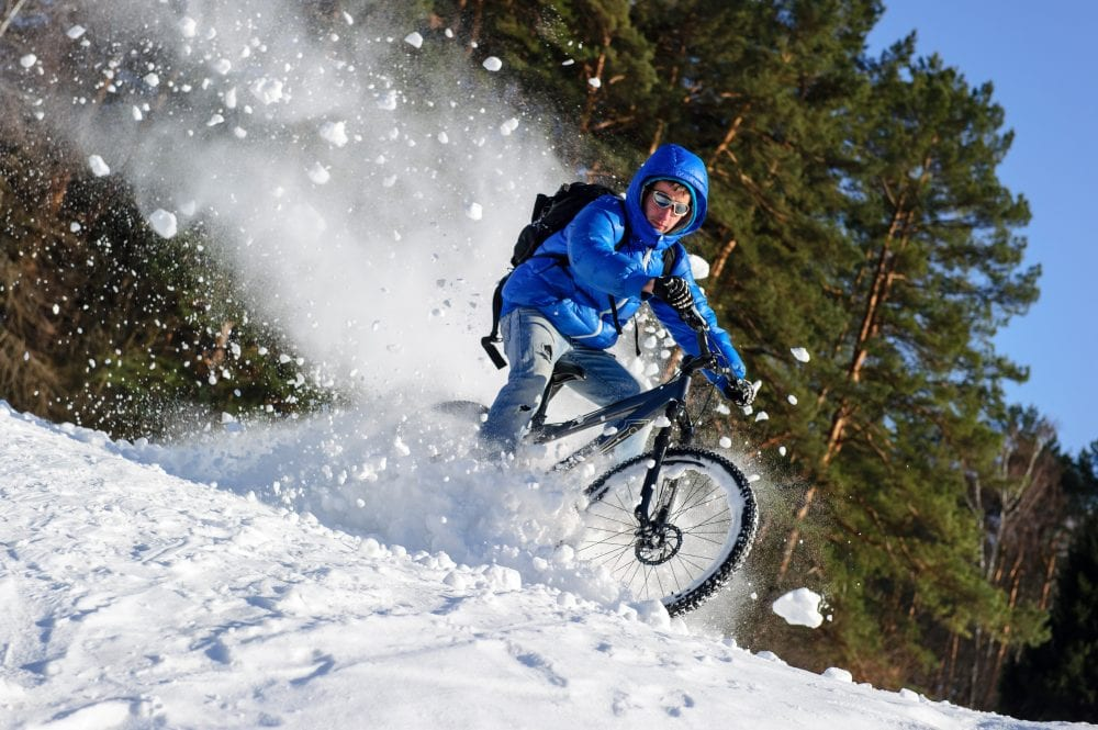 Rider cycling on mountain bicycle in the snow winter forest