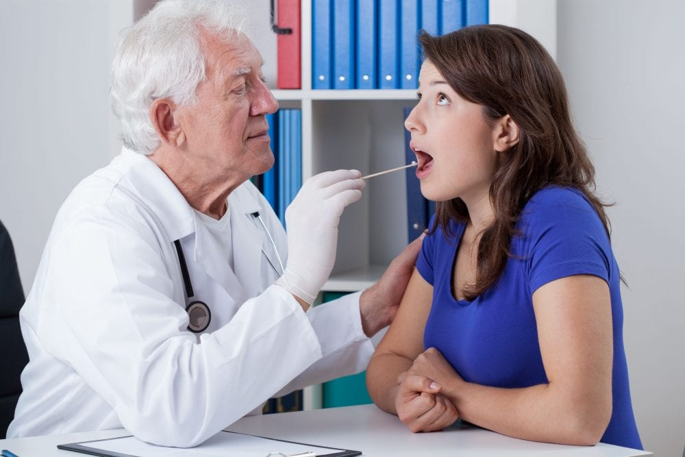 General practitioner examining throat of young woman