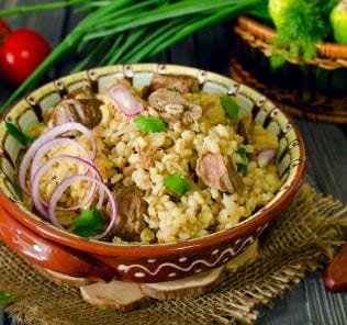 Pearl barley with meat on a wooden table, rustic style