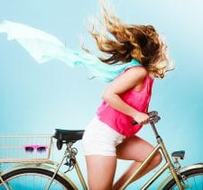 Active woman riding bike bicycle fast against wind. Young girl with hair windblown. Healthy lifestyle and recreation leisure activity. Studio shot.