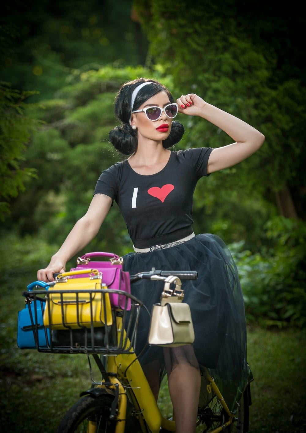 Beautiful girl with retro look wearing a black outfit having fun in park with bicycle. Outdoor lifestyle concept. Vintage scenery. Fashionable brunette with bike and basket with colored purses