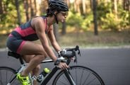 Pretty sportive girl rides a bike on the road on the nature background. She wears black-pink sportswear, a stopwatch, a black helmet, sunglasses and green sneakers. Shoot from the side. Horizontal.