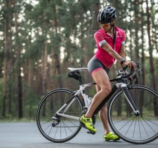 Active girl stands on the bike on the road outdoors. She wears a pink sports jacket, black-pink shorts, sunglasses, black helmet, green sneakers and a stopwatch. Cyclist looks at the back wheel.