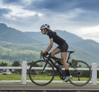 Woman Cyclist riding a Road bike in countryside track with green forest and clear climate ,sport and wellness concept