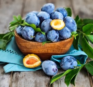 Fresh plums (prunes) in wooden bowl on old wooden background