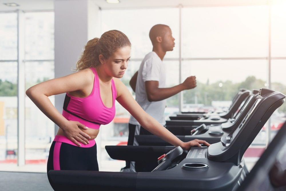 Couple run on treadmills, cardio workout in fitness club. Woman feeling pain Healthy lifestyle, training in gym. Flare effect