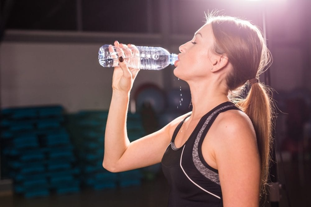 Beautiful fitness woman drinking water from the bottle.