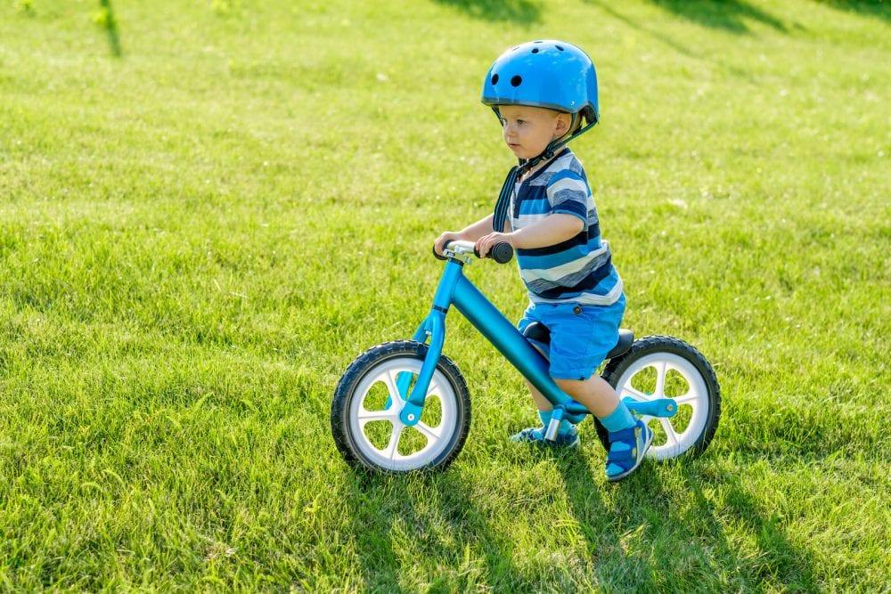 Boy in helmet riding a blue balance bike (run bike)