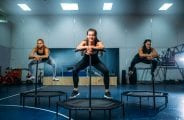 Women on sport trampoline in motion, fitness training. Female teamwork in gym. Aerobic class