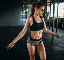 Female athlete exercise with a jump rope in sport gym. Active woman workout in fitness club