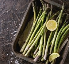 Bundle of young raw uncooked organic green asparagus with sliced lemon and sea salt in old oven tray over brown texture background. Top view. Healthy eating