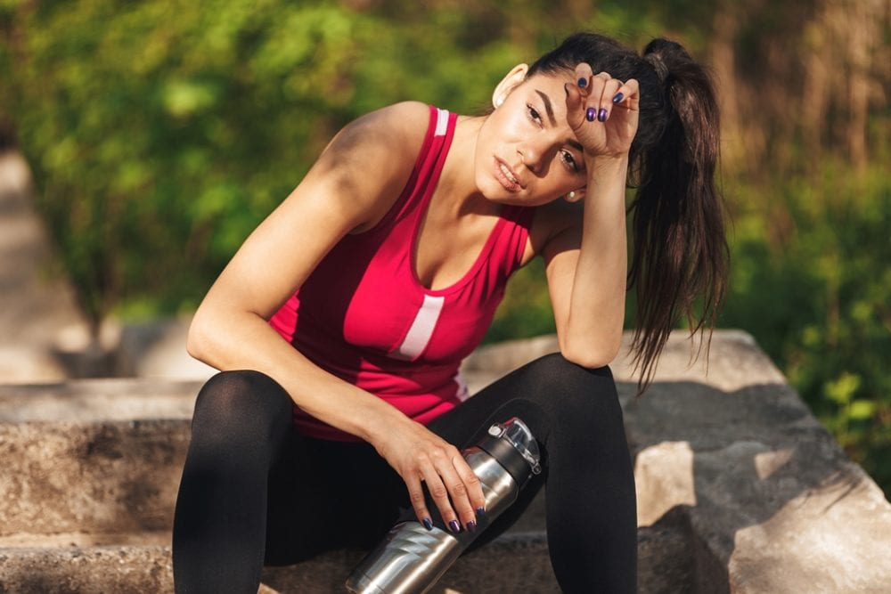 Tired young sportswoman holding water bottle while sitting on steps outdoors