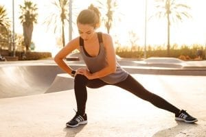 Photo of young amazing sports woman make stretching exercises outdoors on the street.