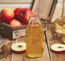 Apple cider vinegar. Glass Bottle of apple organic vinegar on wooden table. Healthy organic drink food. Bottle of fresh cider near autumn red apples. Rustic background,  Space for text