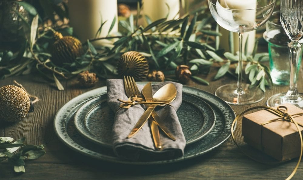 Christmas or New Years eve celebration party table setting. Plates, golden cutlery, festive branch decoration, candles and gliterring toys over wooden table background, selective focus