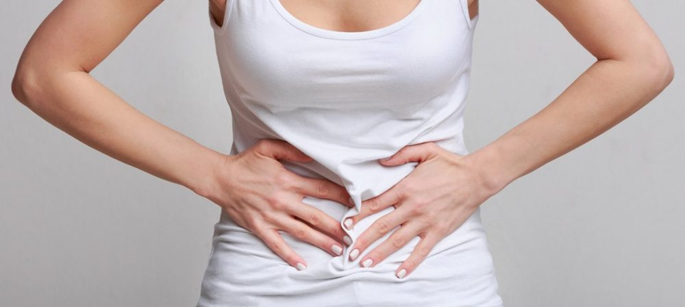 Woman with stomachache, having food poisoning or menstrual period cramp over grey background